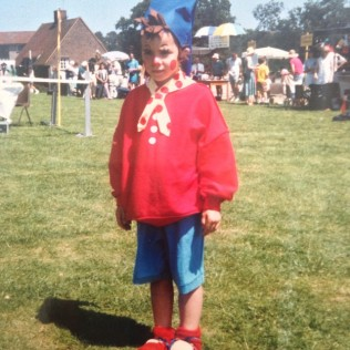 Little girl looking fairly unhappy that she's been dressed up as the character Noddy.