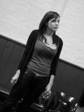 Black and white image of actress wearing tight shirt at an audition.