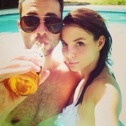 Hot girl with smug guy drinking a bottle of beer in a pool.