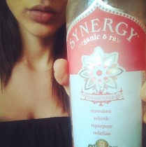 Girl with sexy lips holding up a bottle of Synergy to the camera.