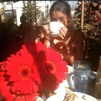 English rose actress drinking tea with red flowers in front of her.