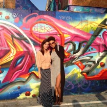 Two pretty girls in front of some graffiti.