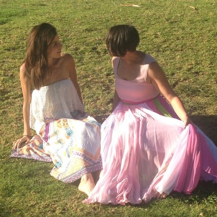 Two girls in long dresses lying on the grass.