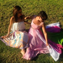 Two girl in long dresses lying on the grass.