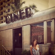 Hot girl standing outside a diner.
