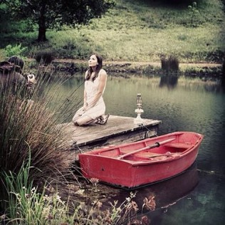 Pretty girl kneeling by a quiet river next to a red rowing boat.