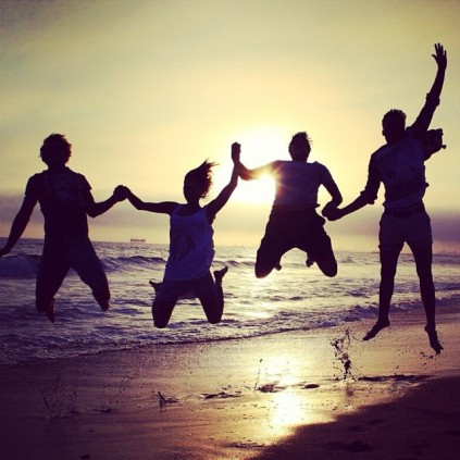 Silhouettes of four friends jumping up in the air in front of a sun set on a beach.