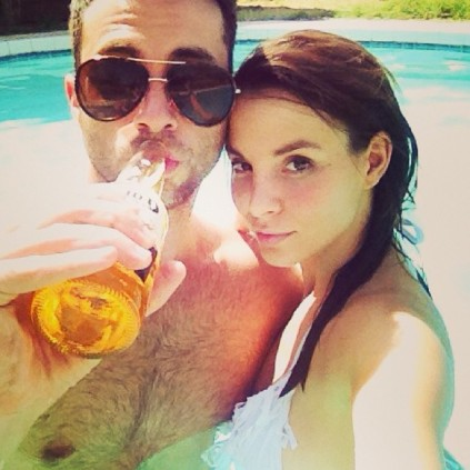 Hot girl with smug guy drinking bottle of beer in a pool.