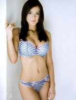 Kacey Barnfield standing a striped bra and panties.