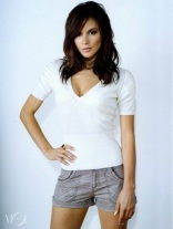 Kacey Barnfield wearing a white shirt and jean shorts placing her hand on her hips.