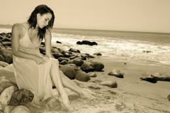 Actress Kacey Barnfield sat on the rocks in front of a beach.