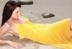 Kacey Barnfield lying on a beach wearing a yellow dress.