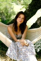 Kacey Barnfield looking pretty sat in a hammock wearing along dress.