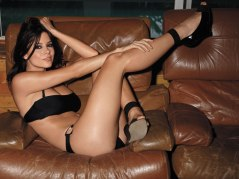 Hot actress lying on a couch in a black bikini swimsuit with a long leg in the air.