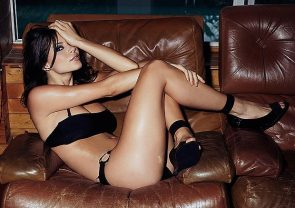 Sexy actress lying on a couch wearing a skimpy black bikini.