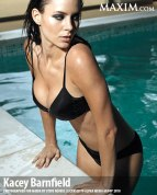 Stunning actress emerging from a pool wearing a black bikini swimsuit.