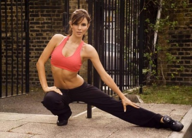 Kacey Barnfield limbering up in a pink sports bra and black sweatpants