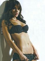 Kacey Barnfield leaning back against the wall in a bra and panties.
