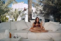 Actress Kacey Barnfield sitting on a big white couch while wearing a brown bikini swimsuit.