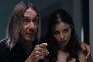 Iggy Pop pointing something out to actress Kacey Barnfield.