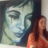 Actress standing in front of a painting of herself.