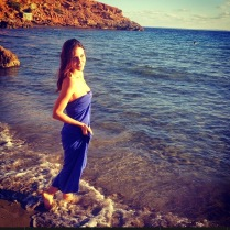Beautiful actress standing on a beach in a blue dress.