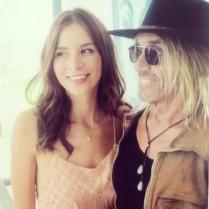 Pretty actress smiling next to Iggy Pop.