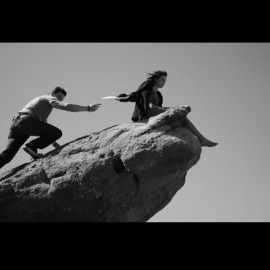 Black and white image of actress on top of a cliff being handed a script.