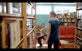 Kacey Barnfield walking to Michael Worth in a library.