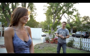 Actress Kacey Barnfield standing in front of actor Michael Worth.