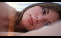 Close-up of actress Kacey Barnfield in bed.