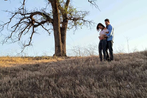 Long shot of actress Kacey Barnfield and actor Michael Worth next to a tree.