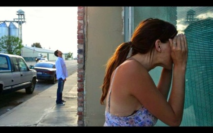 Actress Kacey Barnfield lookng through a window.