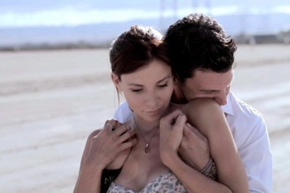 Actress Kacey Barnfield being hugged from behind by actor Michael Worth.