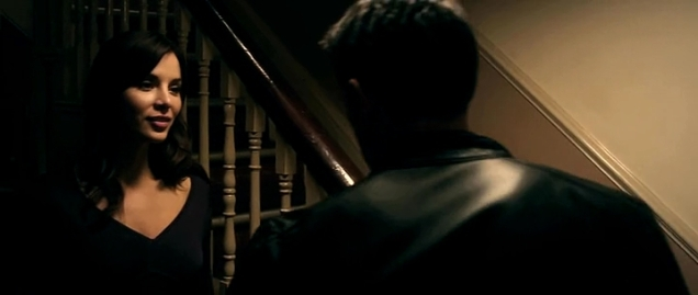 Actress standing at the bottom of stairs opposite Scott Adkins.