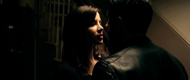 Actress standing at the bottom of stairs embracing Scott Adkins.