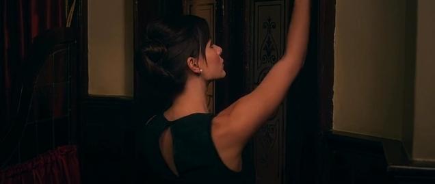 Actress reaching up to bolt London pub doors.