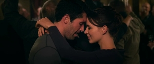 Happy actress with her arms around Scott Adkins' neck.