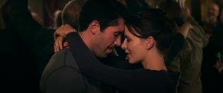Happy actress with her arms around Scott Adkins' neck.