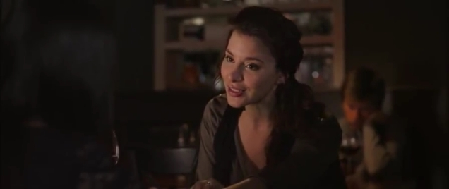 Actress explaining something while sat at a table in a diner.