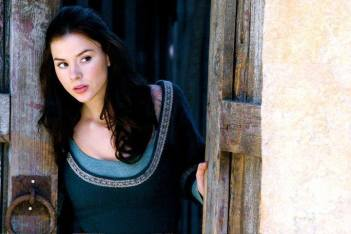 Photo of actress Kacey Barnfield peering around a door while wearing a medieval style dress.