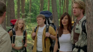 Actress standing in woods with a bunch of friends wearing rucksacks.