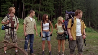 Group standing in the clearing of a forest looking to their right.