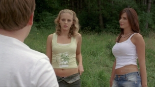 Kacey and Angelica Penn wearing skimpy shirts looking unimpressed.