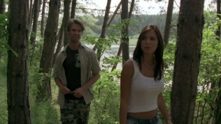 Actress walking through the woods with Nils Hognestad behind her.