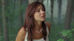 Actress looking upset in the woods.