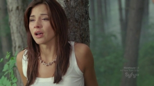 Actress looking distraught in the woods.