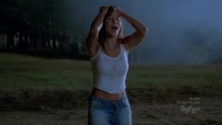 Hot actress wearing skimpy a white shirt looking distraught at night.