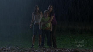 Hot actress in wet white shirt next to family at night.
