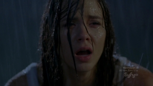 Close-up of pretty actress looking traumatized in the rain at night.